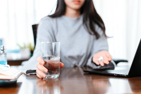 Businesswomen working at home with glass of water takes white round pill in hand.