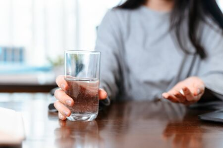 Businesswomen working at home with glass of water takes white round pill in hand. 스톡 콘텐츠