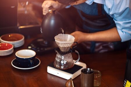 barista pouring boiling water from kettle to drip coffee maker. Archivio Fotografico