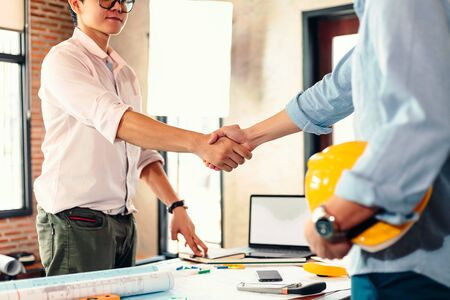Architect and businessman handshake after finish an agreement in the office at  site construction.