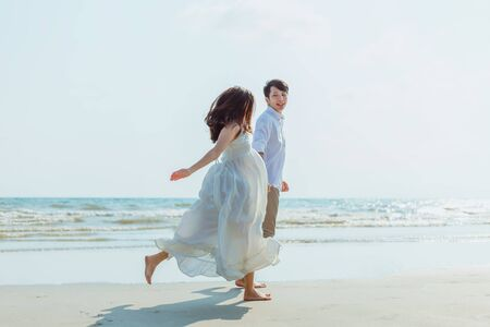 Romantic couple holding hands running and walking on beach. Man and woman in love. People travel concept.