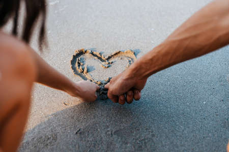 Romantic couple draw heart shapes in the sand on the beach. Banque d'images - 151013471