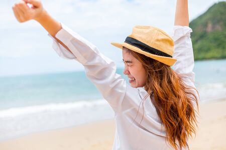 Woman raise hand up on the beach. Happy woman wearing hat.