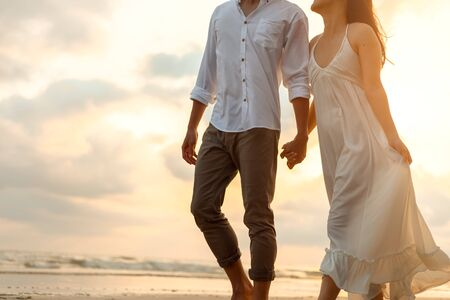 Romantic couple holding hands and walking on beach. Man and woman in love.