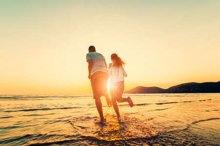Happy couple running and hand hold on the beach between sunset. Couple Honeymoon concept. Stock Photo
