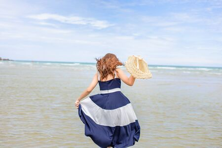 Woman barefoot hold hat and walking on summer along wave of sea water and sand on the beach.