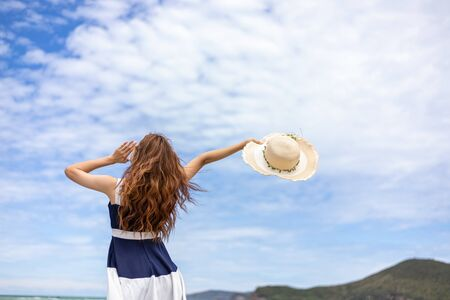 Young girl raise a hat in the sky on the beach. Summer vocation island.
