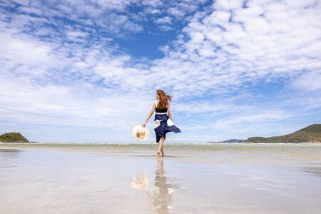 Woman barefoot walking on summer along wave of sea water and sand on the beach.