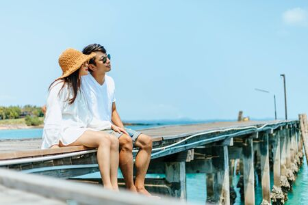 Honeymoon travel couple romantic  hugging and sitting on wood bridge and enjoys their tropical holiday. couple legs hanging over the sea.
