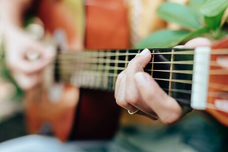woman's hands playing acoustic guitar have fun outdoor, close up. 写真素材
