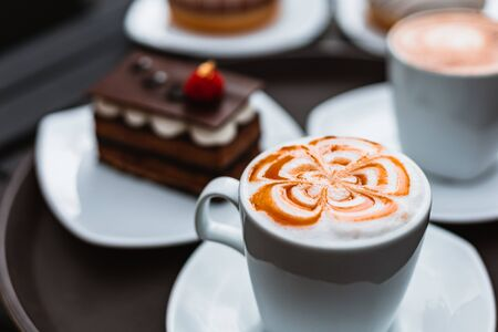cup of a fresh caramel latte with whipped cream on the table and chocolate cake.