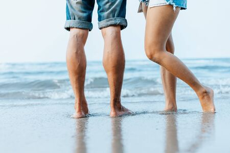 Legs of  couple stand together on beach. Man and woman in love.