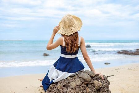 young woman barefoot ware hat and sitting on stone see wave of sea water and sand on the beach.  写真素材