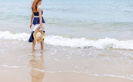 Happy young girl hold hat and walking on the beach. Summer travel, vocation, holiday concept.