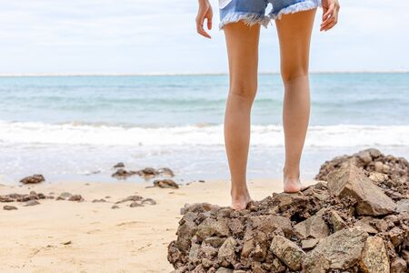 The woman's legs stand on the rocks in the beach