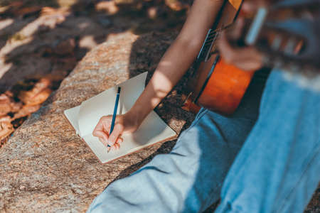 songwriter create and writing notes,lyrics in the book on stone at parks.