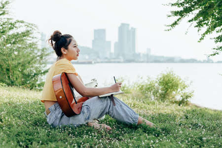 songwriter create and writing notes,lyrics in the book on grass at parks beside the sea and building city background.