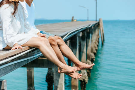 couple legs hanging over the sea and hold hands together on holiday.