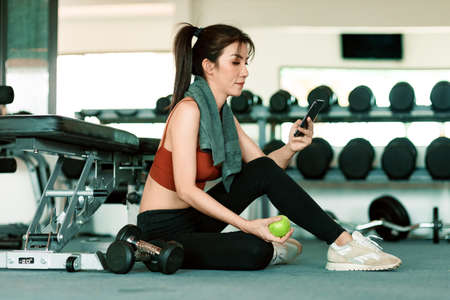 A girl hold green apple using smartphone in fitness gym. Woman exercise in gym fitness breaking and relax.