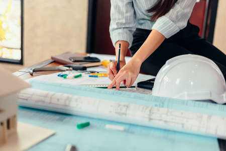 Engineer woman read drawing blue print on table workplace at room site construction. Engineer architect plan concept.