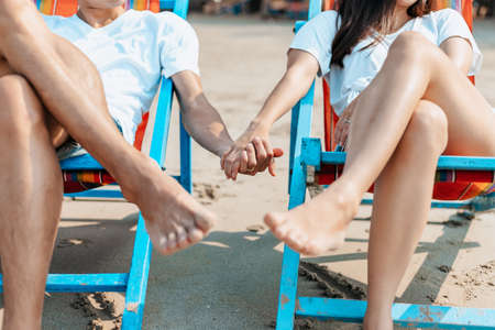 Couple sitting on the deck chairs at the beach. honymoon, Love, travel or vacation concept.