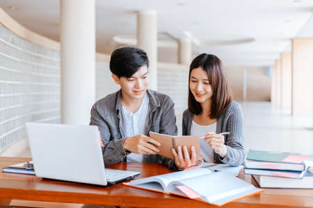 High school or college students  group catching up workbook and learning tutoring on desk and reading, doing homework, lesson practice preparing exam.