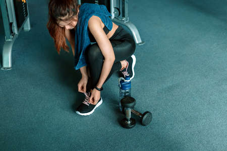 woman's hands tying shoelaces on sport sneakers in gym. dumbbell and water bottle on the ground around the sport girl.