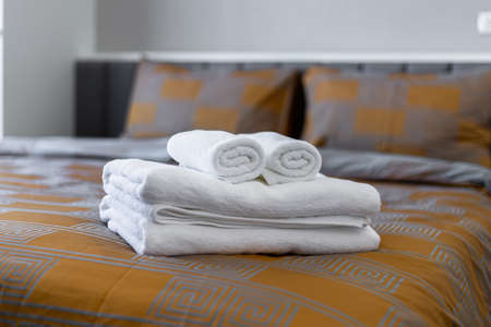 White bath towels on bed in hotel.