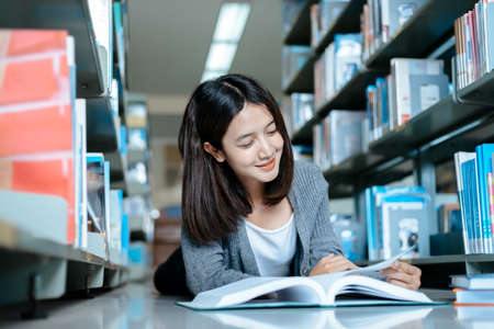 Student college opening and reading a book at library.
