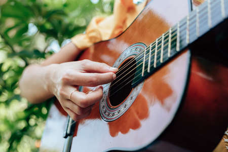woman's hands playing acoustic guitar have fun outdoor, close up. Фото со стока