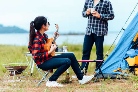 Group of friends camping and they are sitting playing guitar. Camp and music guitar concept.