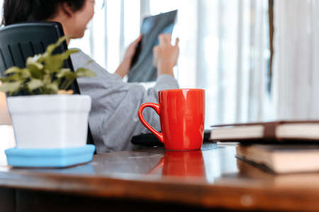 woman working on laptop and hold cup of coffee while sitting at working place.