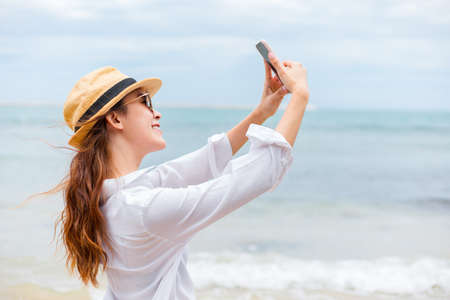 Happy young women wearing  sun glasses use mobile phones to take pictures on the beach While traveling.
