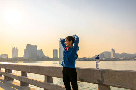 Young sport woman tying hair before her running and city background in the morning.