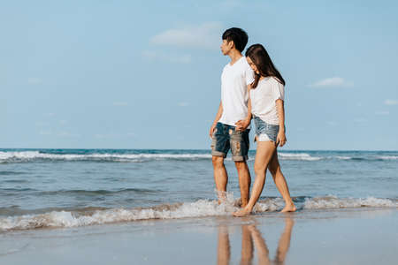 Romantic couple holding hands and walking on beach. Man and woman in love. Standard-Bild
