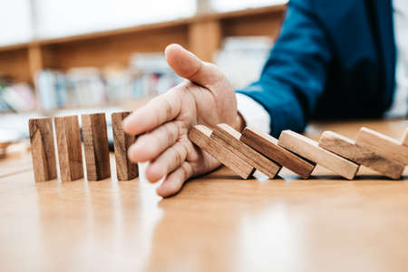 Businessman protect wooden block fall to planning and strategy in risk to business Alternative and prevent.