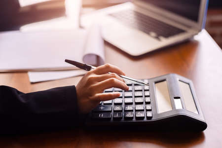 Business women  working with calculator and  business document on office table in office. finance accounting concept.