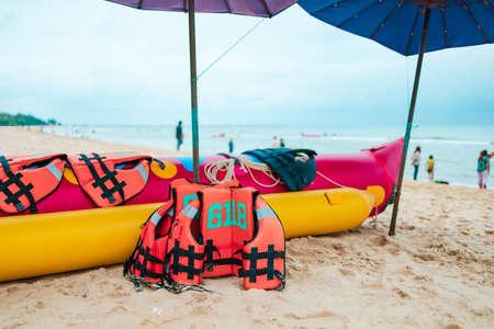 life jacket and banana boat lays on the beach under umbrella.