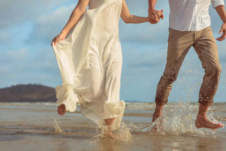 Young couple holding hands and running on the beach.