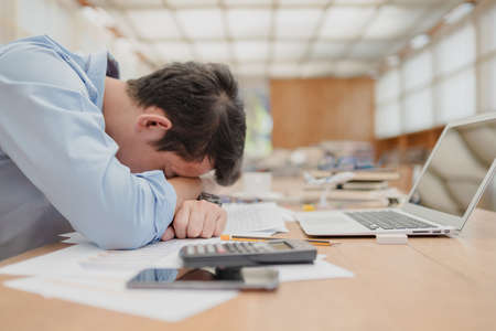 handsome businessman sleepy before working with laptop at desk in office. Working late night and start working early in the morning.