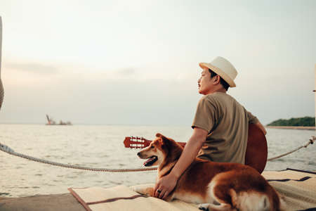 A man wear straw hat and hug with a dog relax near the sea sunset.