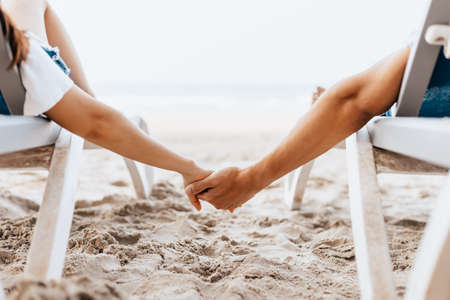 Couple of lovers sitting on beach chair holding hands on the beach in the morning. Newlywed couple on a romantic vacation Archivio Fotografico