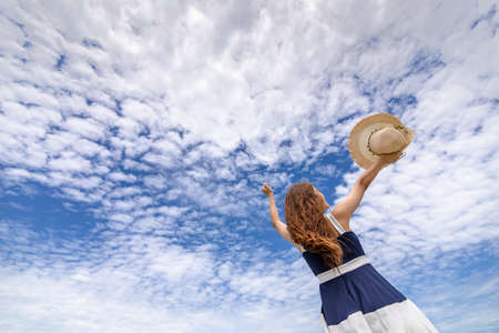 Young woman raise a hat in the sky on the beach. Summer vocation island.