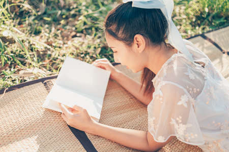 A girl read a novel on straw mat in the forest and light of sunset in the forest. reading hobby and picnic concept.