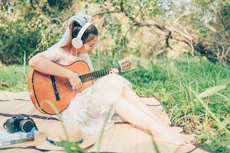 Girl wearing headphone to listen music and playing guitar in the forest. Music hobby and picnic concept. Banque d'images