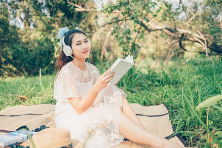 A girl in headphone listen music and read novel in the forest. hobby and picnic concept. Banque d'images