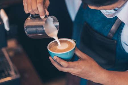 Barista making cappuccino, bartender prepare coffee drink at coffee shop .