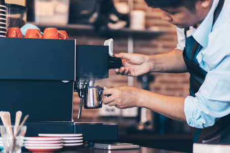 Barista heats milk steam for making lattes at coffee shop. Banque d'images