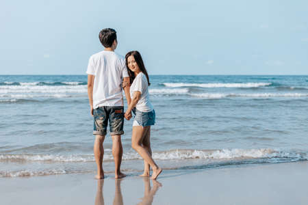 Romantic couple holding hands and stand together on beach. Man and woman in love. Banque d'images