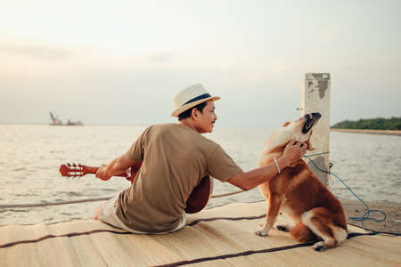 A man wear straw hat and playing guitar music song near the sea sunset and stroking the head dog pet.Travel, Vocation, Holiday concept.
